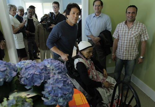 Detroit Free Press columnist Mitch Albom shows Texana Hollis, a 101-year-old Detroiter who was evicted from her foreclosed house, in her remodeled home in Detroit, Wednesday, April 4, 2012. Albom and his charity S.A.Y. Detroit are helped to renovate Hollis' house. Hollis was evicted Sept. 12 and her belongings placed outside after her 65-year-old son failed to pay property taxes linked to a reverse mortgage and HUD foreclosed. (AP Photo/Carlos Osorio)