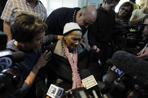 Detroit Free Press columnist Mitch Albom, left, holds Texana Hollis, as she thanks volunteers for fixing her home in Detroit, Wednesday, April 4, 2012. Hollis, a 101-year-old Detroiter was evicted from her foreclosed house Sept. 12 after her 65-year-old son failed to pay property taxes linked to a reverse mortgage and HUD foreclosed. Albom and his charity S.A.Y. Detroit helped to renovate Hollis' house. (AP Photo/Carlos Osorio)