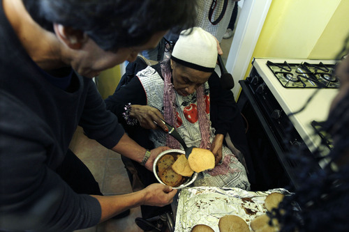Texana Hollis serves cookies in her remodeled home in Detroit, Wednesday, April 4, 2012. Hollis, a 101-year-old Detroiter was evicted from her foreclosed house Sept. 12 after her 65-year-old son failed to pay property taxes linked to a reverse mortgage and HUD foreclosed. Detroit Free Press columnist Mitch Albom and his charity S.A.Y. Detroit helped to renovate Hollis' house. (AP Photo/Carlos Osorio)