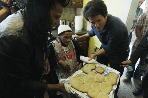 Detroit Free Press columnist Mitch Albom, right, helps Texana Hollis pull cookies from the oven in her home in Detroit, Wednesday, April 4, 2012. Hollis, a 101-year-old Detroit native was evicted from her foreclosed house Sept. 12 after her 65-year-old son failed to pay property taxes linked to a reverse mortgage and HUD foreclosed. Albom and his charity S.A.Y. Detroit helped to renovate Hollis' house. (AP Photo/Carlos Osorio)