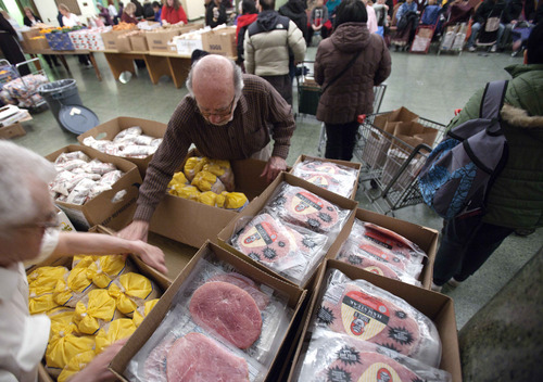 In this Thursday, March 29, 2012 photo, Paul Farris, second from left, of Boston, distributes hams and chickens in the Franciscan Food Center food pantry at St. Anthony Shrine in Boston. Ham prices have been higher than usual for the past two years because the cost of pig feed has gone up. (AP Photo/Michael Dwyer)