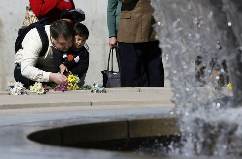Francisco Kjolseth  |  The Salt Lake Tribune Placing flowers, Brian Hoopes of Taylorsville holds on to his son Patrick, 3, who needs to stay within a tethered distance for his intravenous fluids since he was essentially born without intestines. On Wednesday, Patrick ceremoniously started the Celebration of Life Monument fountain on Library Square in Salt Lake which is dedicated to those who have given the gift of life through organ, eye, tissue and blood donation. Patrick has been on the donor list for a small intestine for three years.