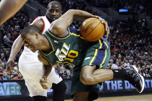 Utah Jazz guard Alec Burks, right, loses his balance driving to the basket against Portland Trail Blazers guard Raymond Felton during the first quarter of their NBA basketball game in Portland, Ore., Monday, April 2, 2012. (AP Photo/Don Ryan)