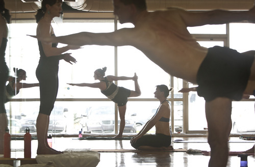 Leah Hogsten  |  The Salt Lake Tribune Students of Bikram Yoga in Sandy sweat through 26 postures and two breathing exercises in 90 minutes under the watchful eye of instructor Jackie Wheeler, left.