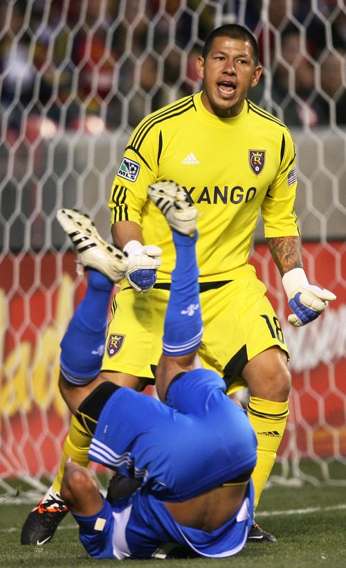Steve Griffin/The Salt Lake Tribune   RSL goal keeper Nick Rimando screams at his defense as Montreal's  Lamar Neagle tumbles past him during the RSL versus Montreal soccer game at Rio Tinto Stadium in Sandy Wednesday April 4, 2012.