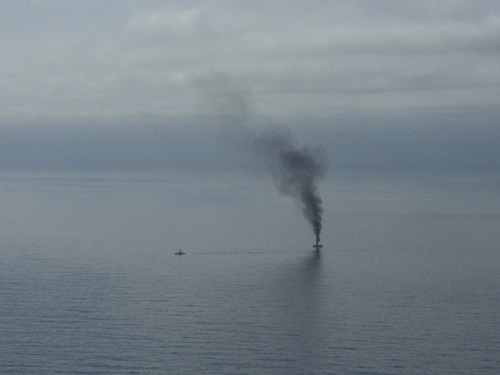 A giant plume of smoke rises from a derelict Japanese ship after it was hit by canon fire by a U.S. Coast Guard cutter on Thursday, April 5, 2012, in the Gulf of Alaska. The Coast Guard decided to sink the ship dislodged by last year's tsunami because it was a threat to maritime traffic and could have an environmental impact if it grounded. (AP Photo/Mark Thiessen)