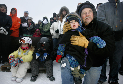 Scott Sommerdorf | Tribune file photo David Schwobe (right) tries to keep his grandson Max Schwobe (2 years old), warm during the  2009 Easter Sunrise Service atop Snowbird's 12,000 foot Hidden Peak as others huddle around the firepit. This year's service takes place 7 a.m. Sunday.