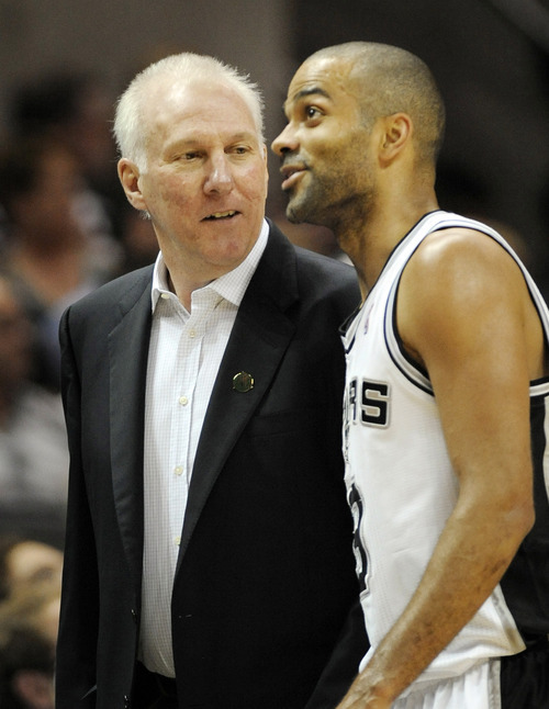 San Antonio Spurs head coach Gregg Popovich, left, talks to Spurs' Tony Parker, of France, during the first half of an NBA basketball game against the Utah Jazz, Sunday, April 8, 2012, in San Antonio. (AP Photo/Darren Abate)