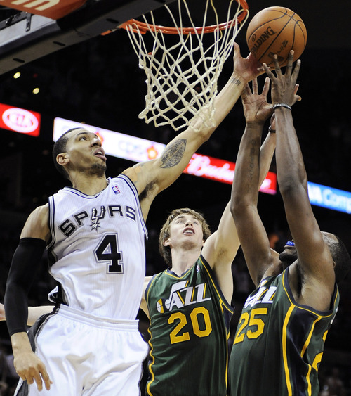 San Antonio Spurs' Danny Green (4) shoots over Utah Jazz's Gordon Hayward (20) and Al Jefferson during the second half of an NBA basketball game, Sunday, April 8, 2012, in San Antonio. San Antonio won 114-104. (AP Photo/Darren Abate)