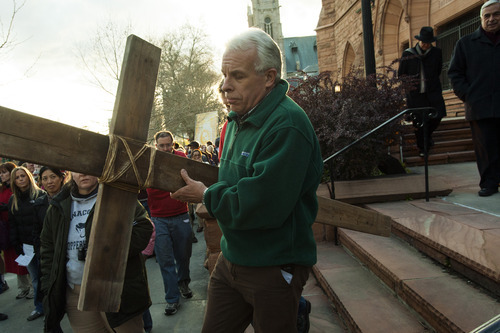 Chris Detrick  |  The Salt Lake Tribune Jim Burke, of Salt Lake City, carries a wooden cross from the Cathedral of the Madeleine to First Presbyterian Church during the Good Friday Procession of the Cross Friday April 6, 2012. Since 1983, the Salt Lake Council of Churches has sponsored this annual procession, which is similar to the tradition of the