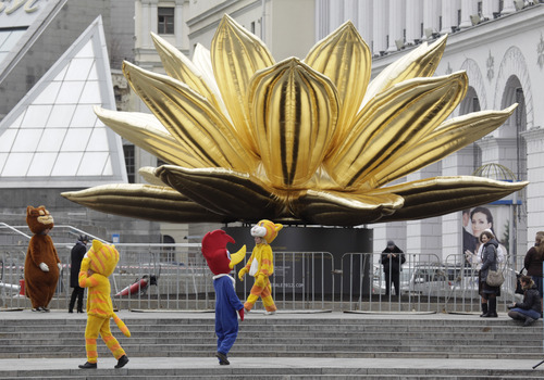 Ukrainians dressed as cartoon characters roam around, in search for clients to pose with for photos, to earn extra money near an inflatable lotus installed by Korean artist Choi Jeong-Hwain at Independence Square in Kiev, Ukraine, Tuesday, April 10, 2012. Kiev is one of Ukraine's four cities which, together with Poland, will co-host the Euro 2012 soccer tournament. (AP Photo/Efrem Lukatsky)