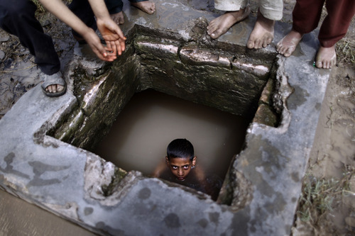A Pakistani boy swims in a water reservoir to cool off as the temperature rises, while others wait their turn, next to a slum area on the outskirts of Islamabad, Pakistan, Tuesday, April 10, 2012. (AP Photo/Muhammed Muheisen)
