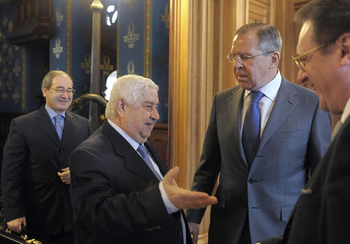 Russian Foreign Minister Sergey Lavrov, second right, speaks with Syrian Foreign Minister Walid Muallemalso, second left, in Moscow on Tuesday, April 10, 2012. Russian Deputy Foreign Minister Mikhail Bogdanov stands at right. Russia on Tuesday called on the opposition as well as countries that