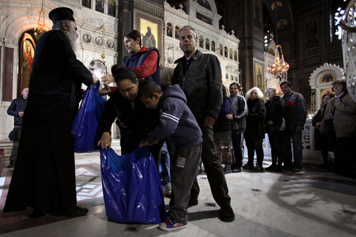 Father Andreas, an Orthodox Christian priest hands out food parcels at Piraeus Cathedral, near Athens on Tuesday, April 10, 2012.  The Orthodox church has stepped up a charity drive to help the unemployed in the crisis-hit country ahead of Orthodox Easter on upcoming Sunday.  (AP Photo/Petros Giannakouris)