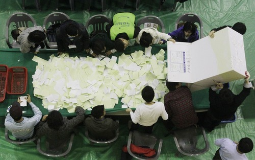 South Korean National Election Commission officials empty a box containing ballots cast in the parliamentary election as they prepare to count them, in Seoul, South Korea, Wednesday, Wednesday, April 11, 2012. (AP Photo/Ahn Young-joon)