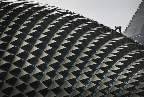 A worker perched on the roof of the Esplanade Theatre carries out the routine cleaning Wednesday, April 11, 2012 in Singapore. (AP Photo/Wong Maye-E)