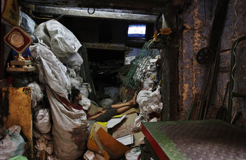 An Indian boy watches television in a shed dumped with garbage in New Delhi, India, Wednesday, April 11, 2012. (AP Photo/Tsering Topgyal)