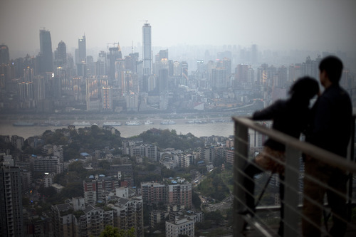 In this Tuesday, April 3, 2012 photo, a couple observe the city skyline at a viewpoint in southwestern China's Chongqing city. Many residents of the Chinese city of Chongqing say they still admire their former leader Bo Xilai despite his dismissal in the biggest political scandal in years. (AP Photo/Alexander F. Yuan)