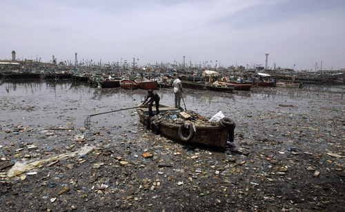 Pakistani scavengers collect flotsam which they can salvage for recycling to make their living, from aboard a small boat in the polluted fishing harbor in Karachi, Pakistan, on Wednesday, April 11, 2012. (AP Photo)
