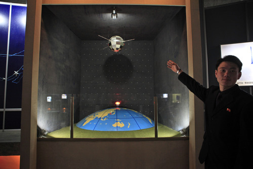 FILE - In this file photo taken Tuesday, April 10, 2012, North Korean guide Kim Won Ho shows journalists a model depicting a North Korean satellite over planet earth at the Three Revolutions exhibition hall in Pyongyang, North Korea. According to North Korea's official version of things, commemorated on postage stamps and re-enacted in mass performances, the country's first venture into space was 14 years ago, when the