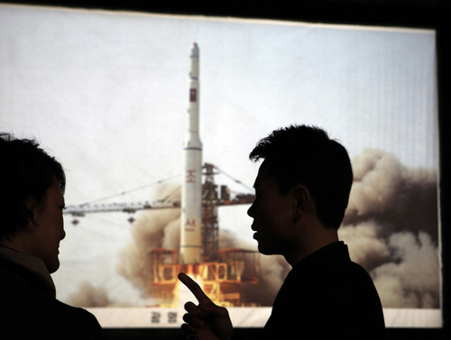 FILE - In this Tuesday, April 10, 2012 file photo, North Korean guide Kim Won Ho, right, speaks to a foreign journalist near a photo depicting the 2009 satellite rocket launch at the Three Revolutions exhibition hall in Pyongyang, North Korea. According to North Korea's official version of things, commemorated on postage stamps and re-enacted in mass performances, the country's first venture into space was 14 years ago, when the
