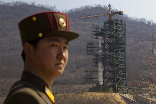 FILE - In this Sunday, April 8, 2012 file photo, a North Korean soldier stands in front of the country's Unha-3 rocket, slated for liftoff between April 12-16, at a launching site in Tongchang-ri, North Korea. According to North Korea's official version of things, commemorated on postage stamps and re-enacted in mass performances, the country's first venture into space was 14 years ago, when the