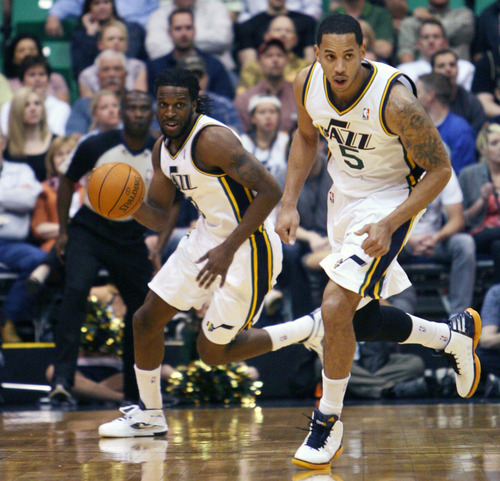 Steve Griffin/The Salt Lake Tribune   Utah's Demarre Carroll, left, and Devin Harris head up court as the run the fast break during first half action in the Jazz versus Spurs game at EnergySolutions Arena in Salt Lake City Monday April 9, 2012.