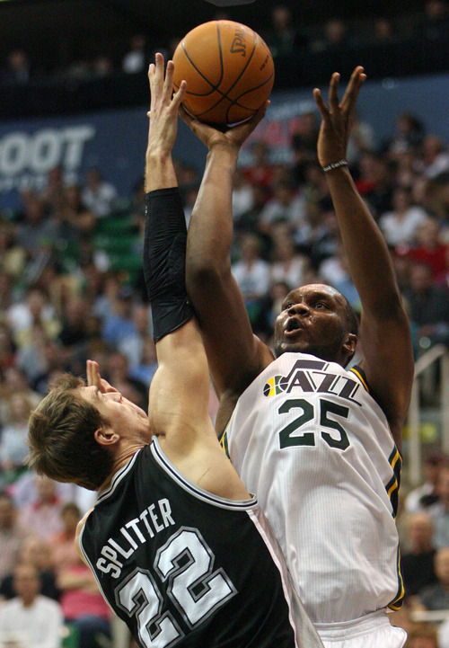 Steve Griffin/The Salt Lake Tribune   Utah's Al Jefferson shoots over San Antonio's Tiago Splitter during second half action in the Jazz versus Spurs game at EnergySolutions Arena in Salt Lake City Monday April 9, 2012.