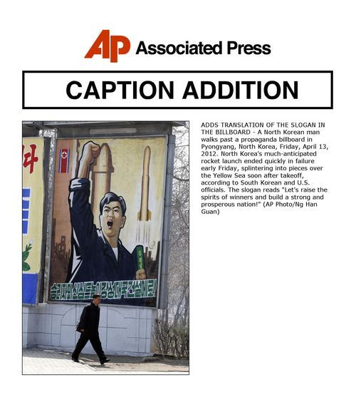 ADDS TRANSLATION OF THE SLOGAN IN THE BILLBOARD - A North Korean man walks past a propaganda billboard in Pyongyang, North Korea, Friday, April 13, 2012. North Korea's much-anticipated rocket launch ended quickly in failure early Friday, splintering into pieces over the Yellow Sea soon after takeoff, according to South Korean and U.S. officials. The slogan reads