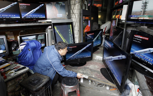 A man watches a TV news showing the computer-generated rocket of North Korea at a home appliance retailer in Seoul, South Korea, Friday, April 13, 2012.  North Korea's much-anticipated rocket launch ended quickly in failure early Friday, splintering into pieces over the Yellow Sea soon after takeoff.  (AP Photo/Lee Jin-man)