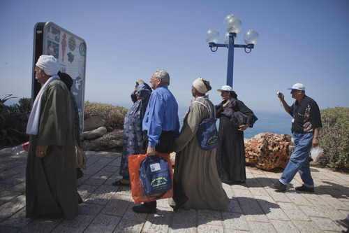 In a photo taken Tuesday, April 10, 2012, Egyptian tourists visit the Old City of Jaffa, Israel. Thousands of defiant Egyptian Christian pilgrims are violating their church's ban against entering Israel to visit religious sites in Jerusalem and other areas controlled by the Jewish state, risking punishment by church officials and potentially, a backlash against the community.(AP Photo/Dan Balilty)