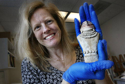 Scott Sommerdorf  |  The Salt Lake Tribune              Bonnie Pilblado, the curator of USU's Museum of Anthropology, holds the figurine recently recently turned over to USU on Thursday. Pilblado is leading the scientific investigation into whether the figurine is actually the long-lost artifact from the Pilling Figurines collections, originally recovered in Range Creek in 1950.