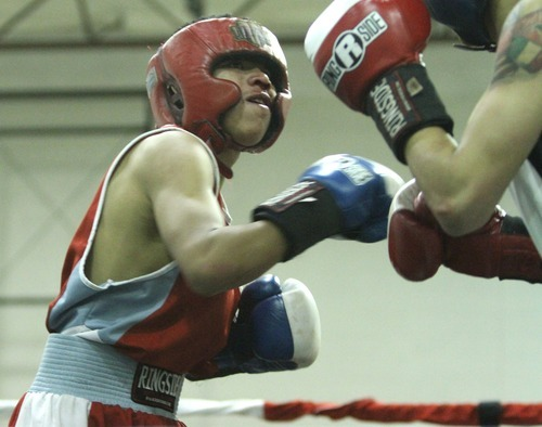 Rick Egan    The Salt Lake Tribune   Jr. Torez, Salt Lake, (red) fights Roberto Perez, Gate City, (white) in the113 lb division, in the Rocky Mountain Golden Gloves Regionals at the Sports Mall in Murray, Saturday, April 14, 2012.