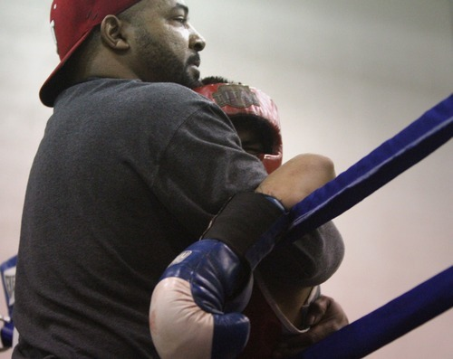 Rick Egan    The Salt Lake Tribune   Jr. Torez, Salt Lake, (red) holds onto his coach after the match was called by the referee, in the113 lb division, in the Rocky Mountain Golden Gloves Regionals at the Sports Mall in Murray, Saturday, April 14, 2012.