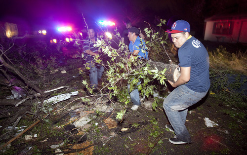 Residents of a south Wichita neighborhood clean up fallen trees after a tornado caused massive destruction in the Wichita, Kan.-area on Saturday night, April 14, 2012. Tornadoes were spotted across the Midwest and Plains on Saturday as an outbreak of unusually strong weather seized the region, and forecasters sternly warned that