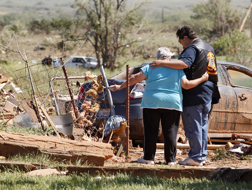 Sue Ogrocki  |  The Associated Press Linda Dupree is hugged Sunday by an unidentified member of the Christian Motorcycle Association after a deadly tornado in Woodward, Okla. Dupree's grandson, and two great-grandchildren were killed when the tornado hit their mobile home.