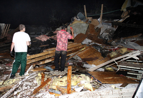 Two men look for people who may be trapped underneath rubble at Pinaire Mobile Home Park after it was struck by a reported tornado, in Wichita, Kan., Saturday night, April 14, 2012. (AP Photo/The Wichita Eagle, Chris Neal)