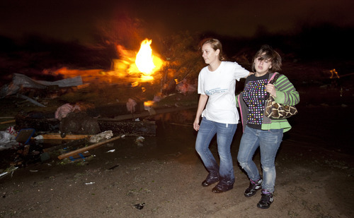 Two people walk past a gas fire in the Pinaire mobile home park in Wichita, Kansas Saturday April 14, 2012 after a tornado caused massive destruction in the area on Saturday night. Tornadoes were spotted across the Midwest and Plains on Saturday as an outbreak of unusually strong weather seized the region, and forecasters sternly warned that