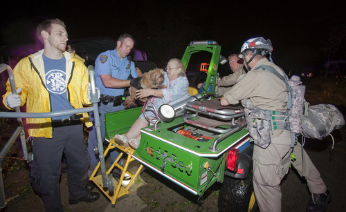An elderly woman and her dog are taken out of the Pinaire Mobile Home Park in Wichita, Kan., after a tornado caused massive destruction in the area, on Saturday night, April 14, 2012. Tornadoes were spotted across the Midwest and Plains on Saturday as an outbreak of unusually strong weather seized the region, and forecasters sternly warned that