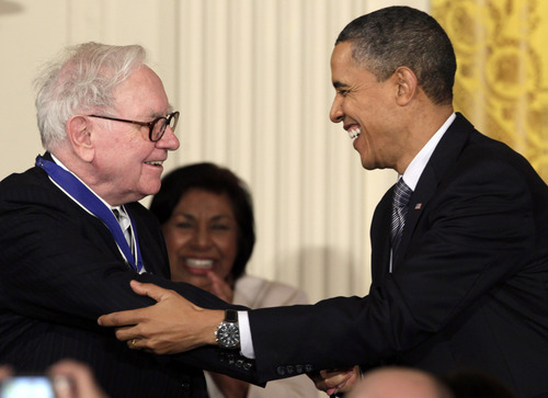 FILE - In this Feb. 15, 2010, file photo President Barack Obama congratulates Warren Buffett after presenting him with a 2010 Presidential Medal of Freedom in an East Room ceremony at the White House in Washington. In his weekly radio and internet address Saturday April 14, 2012, Obama urged Americans to ask their member of Congress to support the