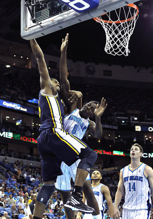 Utah Jazz forward/center Derrick Favors (15) tries to slam dunk over New Orleans Hornets small forward Al-Farouq Aminu (0) in the second half of an NBA basketball game in New Orleans, Friday, April 13, 2012. The Hornets won 96-85. (AP Photo/Gerald Herbert)
