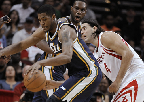 Houston Rockets' Luis Scola (4) reaches around Utah Jazz's Derrick Favors during the second half of an NBA basketball game Wednesday, April 11, 2012, in Houston. Utah won 103-91. (AP Photo/Pat Sullivan)