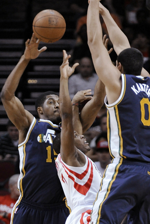 Houston Rockets' Kyle Lowry, center, is sandwiched between Utah Jazz defenders Derrick Favors (15) and Enes Kanter (0) during the first half of an NBA basketball game Wednesday, April 11, 2012, in Houston. (AP Photo/Pat Sullivan)