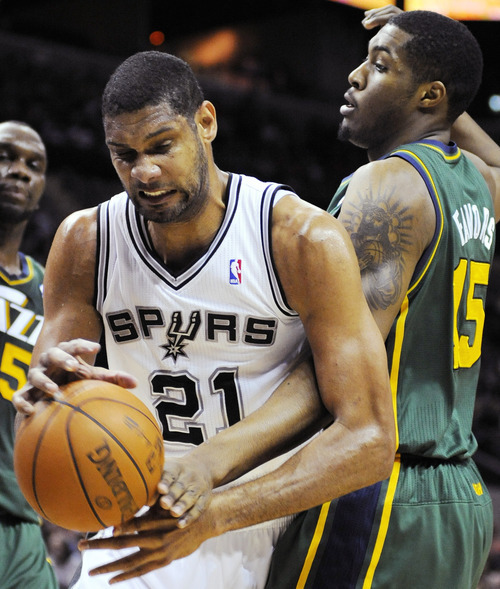 San Antonio Spurs' Tim Duncan (21) fights for a rebound with Utah Jazz's Derrick Favors during the first half of an NBA basketball game, Sunday, April 8, 2012, in San Antonio. (AP Photo/Darren Abate)
