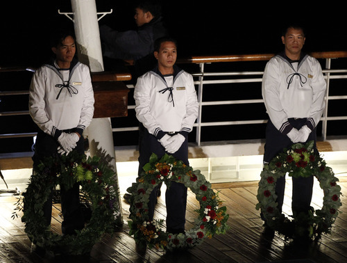 Crew members stand with wreaths during a memorial service, marking the 100th year anniversary of the Titanic disaster, aboard the MS Balmoral Titanic memorial cruise ship, at the wreck site in the North Atlantic Ocean, early Sunday, April 15, 2012.   Cruise ship passengers and crew said prayers Sunday at the spot in the North Atlantic where the Titanic sank 100 years ago with the loss of more than 1,500 lives. (AP Photo/Lefteris Pitarakis)