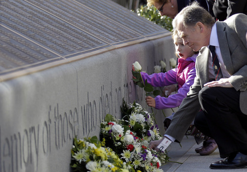 Six-year old Alex Warouaon from Chicago, USA,  who's great-great-great-grandfather died in the Titanic disaster, lays a rose at the Titanic Memorial Plaque during the service at Belfast City Hall, Northern Ireland, Sunday, April 15, 2012 one-hundred years after the Titanic sank. The Titanic passenger liner was built in Belfast, and sank in the North Atlantic Ocean on its maiden voyage from England to New York, USA, in the early hours of April 15, 1912, after colliding with an iceberg and over 1,500 people perished in the sinking. (AP Photo/Peter Morrison)
