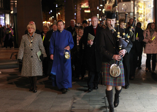 Dean John Mann, second from left, and Northern Ireland Deputy First Minister Martin McGuinness, center, walk behind a lone bagpiper to Belfast City Hall following a Titanic Commemoration service at St. Ann's Cathedral Belfast, Northern Ireland, Saturday, April 14, 2012.  A century after the great ship went down with the loss of 1,500 lives, events around the globe are marking a tragedy that retains a titanic grip on the world's imagination _ an icon of Edwardian luxury that became, in a few dark hours 100 years ago, an enduring emblem of tragedy. (AP Photo/Peter Morrison)