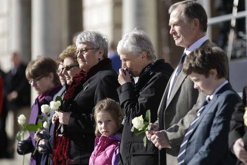 Six-year old Alex Warouaon from Chicago, USA,  who's great-great-great-grandfather died in the Titanic disaster stands with other relatives during a minute silence at the Titanic Memorial Plaque during the service at Belfast City Hall, Northern Ireland, Sunday, April 15, 2012 one-hundred years after the Titanic sank.  The Titanic passenger liner was built in Belfast, and sank in the North Atlantic Ocean on its maiden voyage from England to New York, USA, in the early hours of April 15, 1912, after colliding with an iceberg and over 1,500 people perished in the sinking. (AP Photo/Peter Morrison)