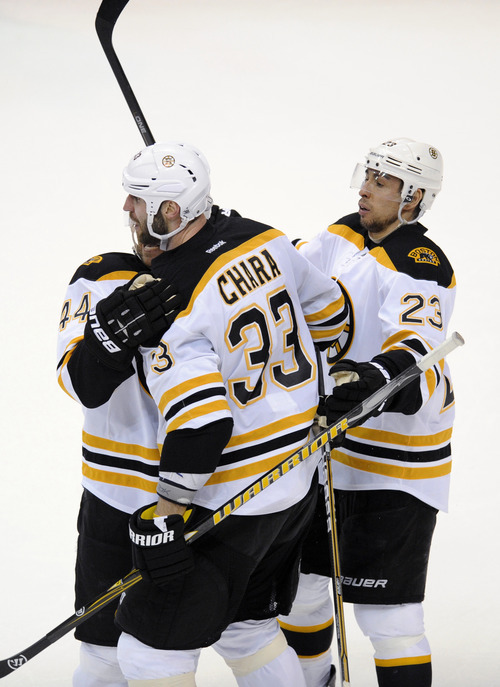 Boston Bruins defenseman Zdeno Chara (33) celebrates his goal with teammates Dennis Seidenberg (44) and Chris Kelly (23) during the third period of Game 3 of an NHL hockey Stanley Cup first-round playoff series against the Washington Capitals, Monday, April 16, 2012, in Washington. The Bruins won 4-3. (AP Photo/Nick Wass)