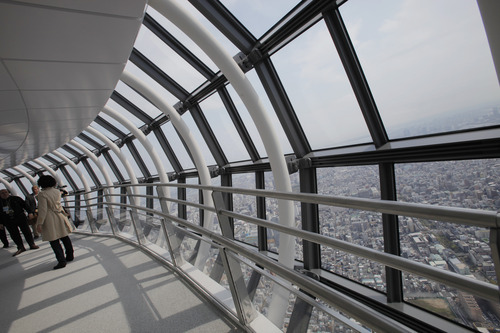 Journalists walk on the 450-meter (1,476 feet)-high observation deck of the Tokyo Sky Tree during a press preview in Tokyo Tuesday, April 17, 2012. The world's tallest freestanding broadcast structure that stands 634-meter (2,080 feet) will open to the public in May. (AP Photo/Itsuo Inouye)